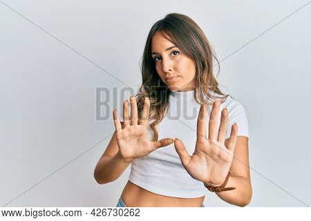 Young brunette woman wearing casual white t shirt moving away hands palms showing refusal and denial with afraid and disgusting expression. stop and forbidden.