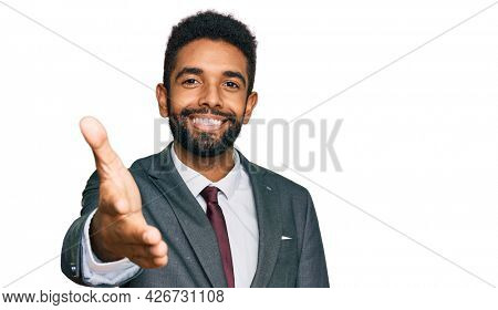Young african american man wearing business clothes smiling friendly offering handshake as greeting and welcoming. successful business.