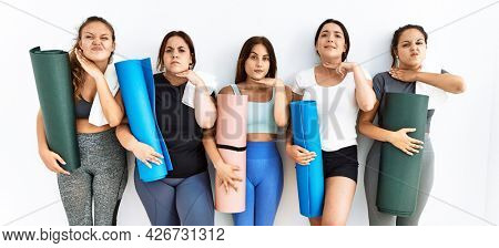 Group of women holding yoga mat standing over isolated background cutting throat with hand as knife, threaten aggression with furious violence