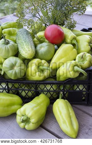 Vegetables In The Box. Fresh Peppers, Cucumbers And Tomatoes In A Box On A Wooden Background. Harves