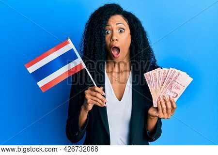 Middle age african american woman holding thailand flag and baht banknotes afraid and shocked with surprise and amazed expression, fear and excited face.