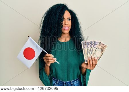 Middle age african american woman holding japan flag and yen banknotes smiling looking to the side and staring away thinking.