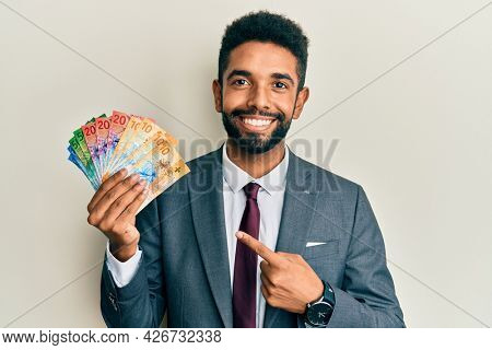 Handsome hispanic business man with beard holding swiss franc banknotes smiling happy pointing with hand and finger