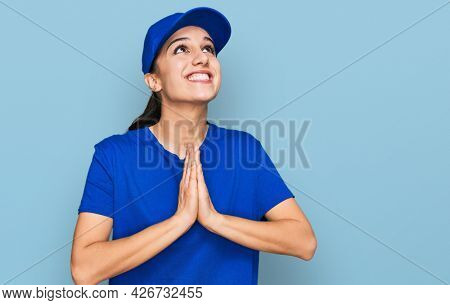 Young hispanic girl wearing delivery courier uniform begging and praying with hands together with hope expression on face very emotional and worried. begging.