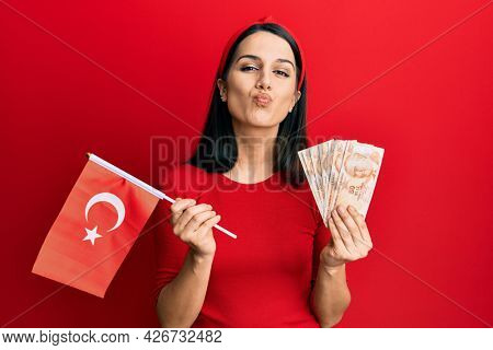 Young hispanic woman holding turkey flag and liras banknotes looking at the camera blowing a kiss being lovely and sexy. love expression.