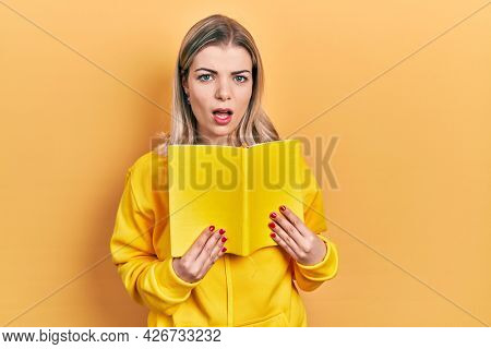 Beautiful caucasian woman holding open book in shock face, looking skeptical and sarcastic, surprised with open mouth