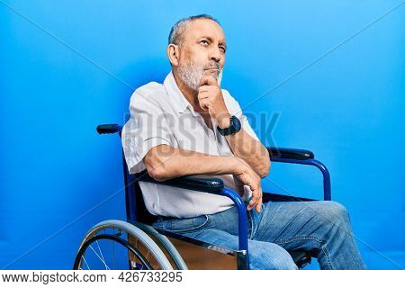 Handsome senior man with beard sitting on wheelchair thinking worried about a question, concerned and nervous with hand on chin