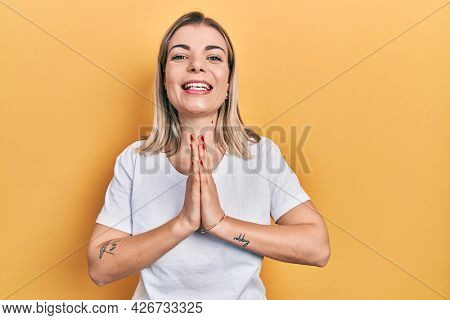 Beautiful caucasian woman wearing casual white t shirt praying with hands together asking for forgiveness smiling confident.