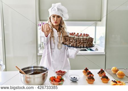 Young caucasian pastry chef woman cooking pastries and cake at the kitchen pointing with finger to the camera and to you, confident gesture looking serious