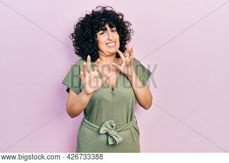 Young middle east woman wearing casual clothes disgusted expression, displeased and fearful doing disgust face because aversion reaction. with hands raised