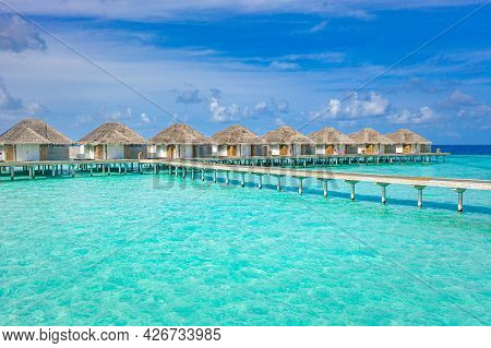 Water Villas In The Turquoise Ocean. View Of The Water Villas At Blue Sunny Sky In The Maldives, The