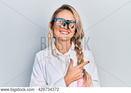 Beautiful young blonde woman wearing optometry glasses smiling cheerful pointing with hand and finger up to the side