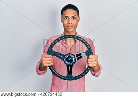 Young african american guy holding steering wheel relaxed with serious expression on face. simple and natural looking at the camera.