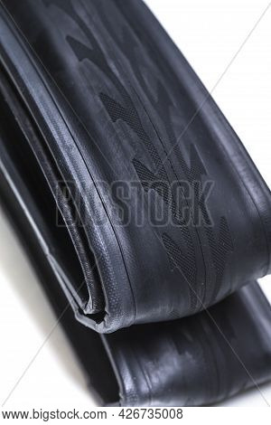 Closeup Of New Folded Road Bike Tyre Over White Background. Vertical Image