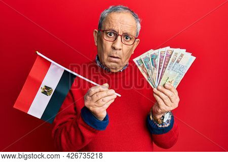 Handsome senior man with grey hair holding egypt flag and egyptian pounds banknotes clueless and confused expression. doubt concept.