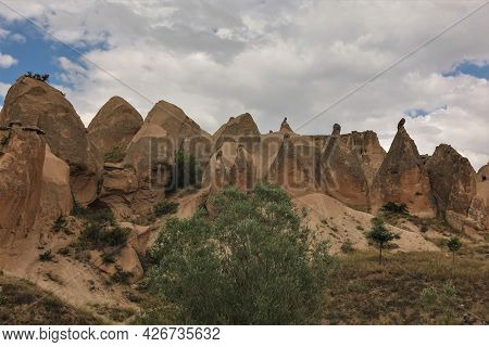 Amazing Landscape Of Cappadocia. Fancy Mountains With Mushroom-shaped Peaks On The Background Of A B