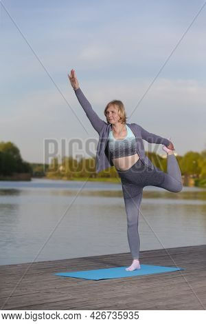 Senior Caucasian Woman In Professional Sport Outfit During Yoga Stretching Training On Wooden Stage