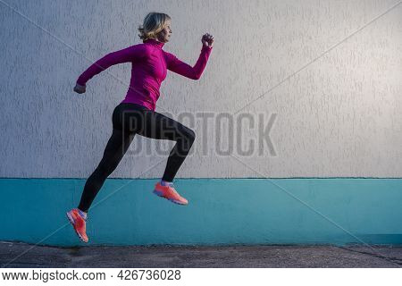Concentrated Running Mature Woman Having Outdoor Jogging Training Against Concrete Wall Background.
