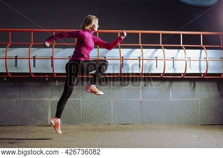 Professional Senior Female Runner In Jogging Outfit During Running Training In Evening City Environm