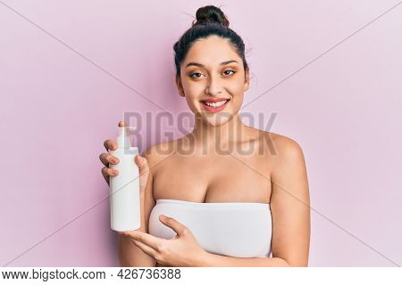 Beautiful middle eastern woman holding cosmetic moisturizer facial cream looking positive and happy standing and smiling with a confident smile showing teeth