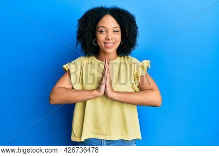 Young african american girl wearing casual clothes praying with hands together asking for forgiveness smiling confident.