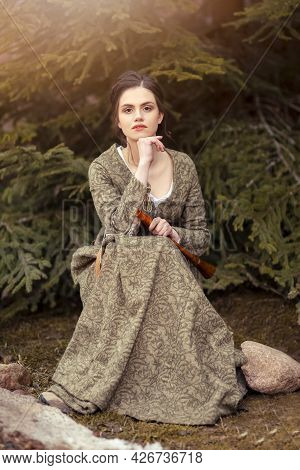Portrait Of Calm Caucasian Female In Old Medieval Green Dress With Flute Against Firtrees Outdoors.