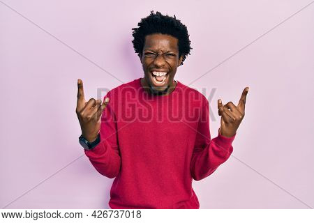 Young african american man wearing casual clothes shouting with crazy expression doing rock symbol with hands up. music star. heavy music concept.