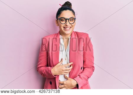 Beautiful middle eastern woman wearing business jacket and glasses smiling and laughing hard out loud because funny crazy joke with hands on body.