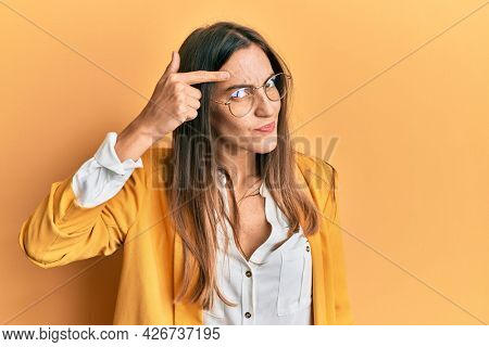 Young beautiful woman wearing business style and glasses pointing unhappy to pimple on forehead, ugly infection of blackhead. acne and skin problem