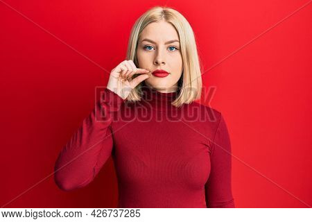 Young blonde woman wearing casual clothes mouth and lips shut as zip with fingers. secret and silent, taboo talking