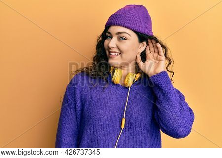 Young brunette woman with curly hair listening to music using headphones smiling with hand over ear listening an hearing to rumor or gossip. deafness concept.