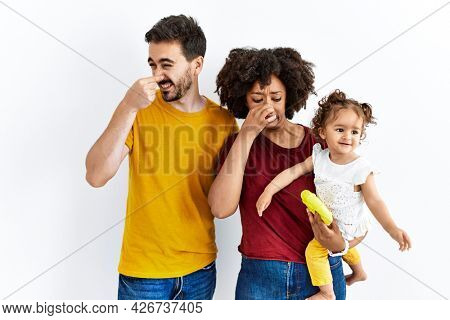 Interracial young family of black mother and hispanic father with daughter smelling something stinky and disgusting, intolerable smell, holding breath with fingers on nose. bad smell