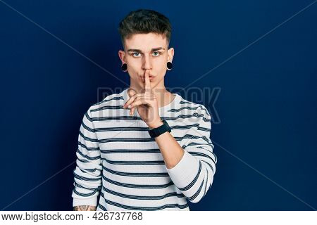 Young caucasian boy with ears dilation wearing casual striped shirt asking to be quiet with finger on lips. silence and secret concept.