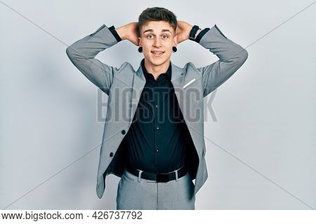 Young caucasian boy with ears dilation wearing business jacket relaxing and stretching, arms and hands behind head and neck smiling happy