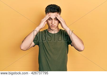 Young caucasian boy with ears dilation wearing casual green t shirt suffering from headache desperate and stressed because pain and migraine. hands on head.