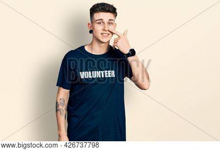 Young caucasian boy with ears dilation wearing volunteer t shirt pointing with hand finger to face and nose, smiling cheerful. beauty concept