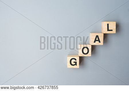 Wooden Cube Block With Goal Business Word. Target, Aim, Mission, Action And Plan Concept