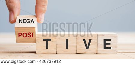 Business Man Hand Holding Wooden Cube With Flip Block Negative To Positive Word On Table Background.