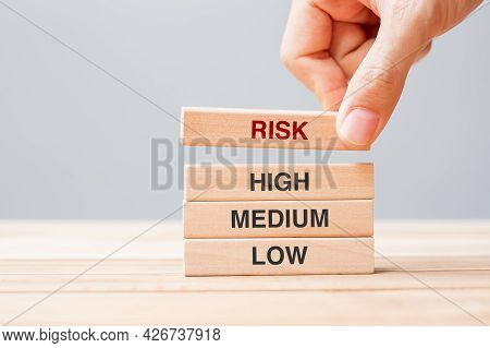 Businessman Hand Placing Or Pulling Wooden Block With Risk Text Over High Medium And Low. Planning,