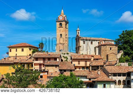 View of old houses and medieval bell tower under blue sky in small town of Monforte d'Alba in Piedmont, Northern Italy.