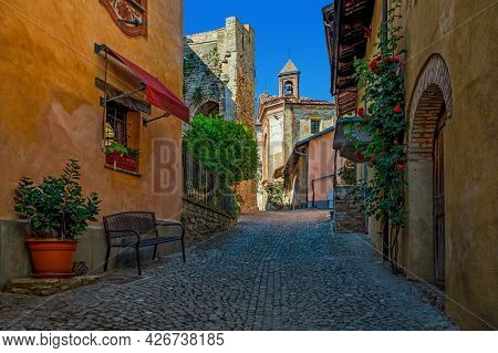 Narrow cobblestone street among colorful houses lead to the small church under blue sky in old town of Monforte d'Alba in Piedmont, Northern Italy.