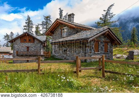 Stone guest houses on green meadow in the mountains in Piedmont, Northern Italy.