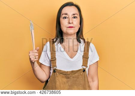 Middle age hispanic woman holding paintbrushes thinking attitude and sober expression looking self confident