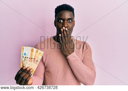 Handsome black man holding 500 philippine peso banknotes covering mouth with hand, shocked and afraid for mistake. surprised expression