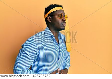 Handsome black man drunk wearing tie over head and sunglasses with hand on stomach because nausea, painful disease feeling unwell. ache concept.