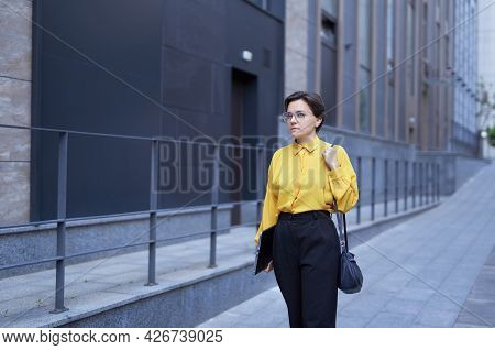Happy Successful Caucasian Brunette Woman In Yellow Blouse And Eyeglasses Going On A Street With Lap