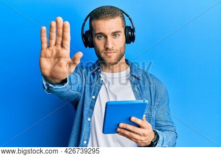 Young caucasian man using touchpad wearing headphones with open hand doing stop sign with serious and confident expression, defense gesture