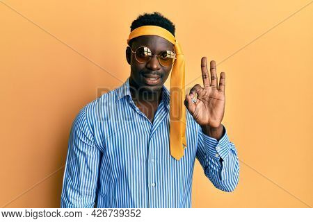 Handsome black man drunk wearing tie over head and sunglasses smiling positive doing ok sign with hand and fingers. successful expression.