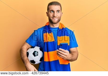 Young caucasian man holding football ball looking at smartphone smiling looking to the side and staring away thinking.
