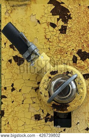 Yellow Old Fragment Of A Gas Station . Fuel Supply Hose Or Handle Switch Switch, Old Shabby Vintage